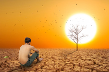 man sit on cracked earth near dry land and hot dry air.