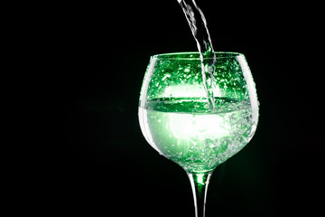 Pouring water in the wine glass with green background