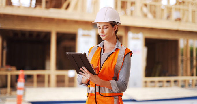 Young woman construction manager directing traffic in front of project. Successful woman using tablet to help manage crew.