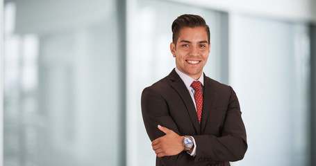 Happy smiling young Hispanic businessman standing in office with arms crossed looking at camera. Copyspace or copy space next to business professional with smile on his face