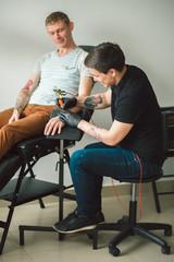 Master tattoo artist in gloves makes tattoo on hand men. Art concept