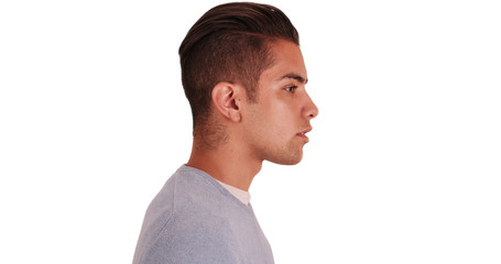 Side view of Hispanic man with cool undercut standing with white background. Profile close up portrait of Latino millennial