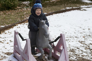 Funny toddler riding toy horse on the outdoor playground