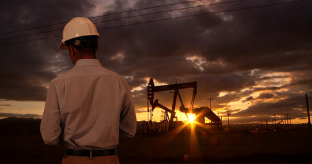 Engineer wearing hard hat helmet checking oil derrick field. Sunset as man looks at oil pump rig