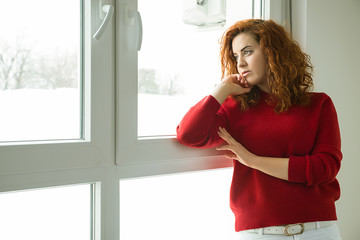 Red-haired girl by the window