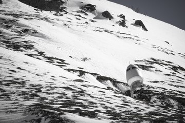 view on beautiful snowcapped rocky mountain range in pyrenees in black and white with snow cannon, france