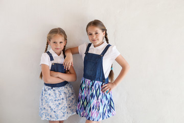 Two girls in fashionable clothes on the background of a textured wall