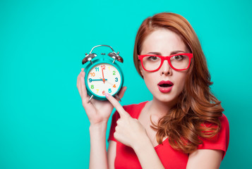 Young beautfiul redhead girl with alarm clock on minty background
