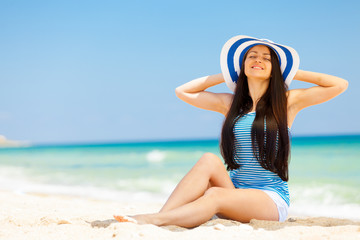 Young brunet girl in hat have a rest on the beach