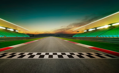 Motion blurred racetrack with start or end line . Night scene .
