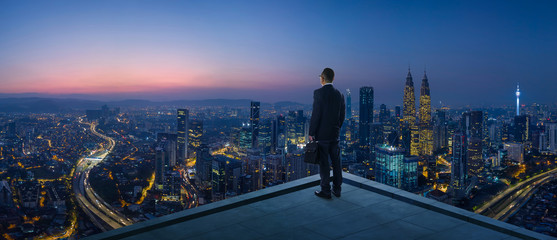 Businessman stand at rooftop looking great cityscape view and thinking business plan of the future . Night scene .
