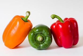 Three bell peppers green in middle isolated on white background