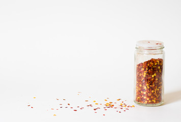 Chili jar with flakes and sprinkles on white background