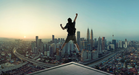 Young man jumping on rooftop with great cityscape sunrise view.