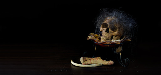 Skull which has hairline on pile of bone in the tray on dark background and wooden floor