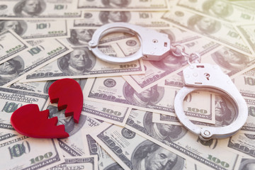 Handcuffs, broken into two halves of a red heart against a background of dollars. division of property in divorce.