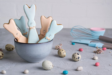 Easter spring decorative composition  with homemade easter cookies in the shape of  a  funny  rabbit, quail eggs and tools necessary to make gingerbread pastry.  Holiday celebration decorations.