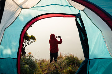 Young woman taking a photo with her phone. View from inside a tent