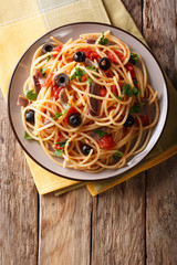Spaghetti alla putanesca with anchovies, tomatoes, garlic and black olives close-up. Vertical top view