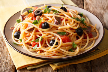 Delicious spaghetti alla putanesca with anchovies with vegetables and greens close-up. horizontal