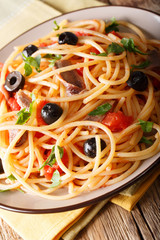 Italian pasta Alla Puttanesca with anchovies, tomatoes, garlic and black olives macro. vertical