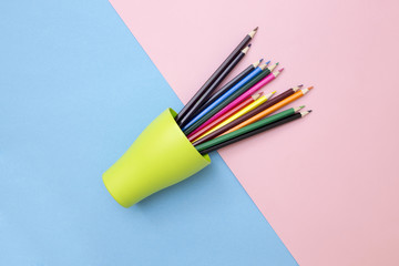 Set of colored pencils in a green cup on a colored background, top view