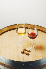 Glasses of white and red wine stand on wooden barrel