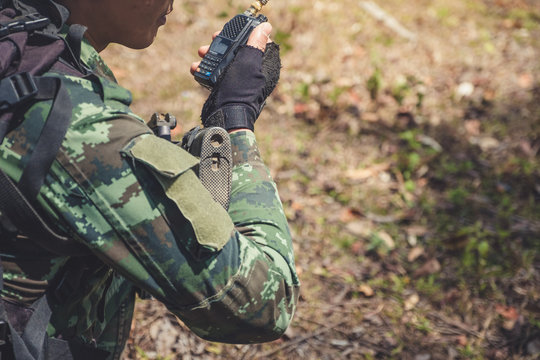 Closeup image of an armed soldier holding and using radio communication in the battle field