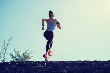 young fitness woman trail runner running up to the top of great wall on mountain
