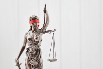 Justitia Figur als Recht Konzept vor Holz Hintergrund