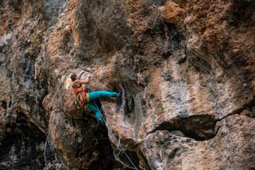Blonde girl climbs rock tufa, side view, Turkey