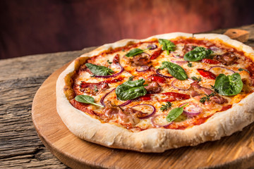Pizza. Tasty fresh italian pizza with bacon cihili pepper spinach and onion served on old wooden table