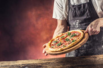 Chef and pizza. Chef offering pizza in hotel or restaurant