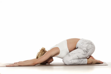 Yoga, sport, training and lifestyle concept - Young blonde woman doing yoga exercise. Portrait of young beautiful woman in white sportswear doing yoga practice