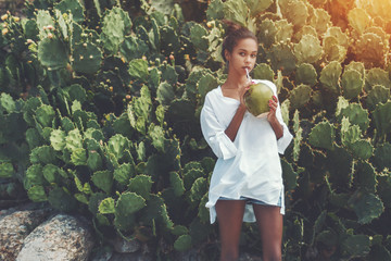 Young sexy Brazilian girl is standing in front of green hedge of cactuses and drinking coconut water from opened fresh coco using straw on sunny summer day, with copy space place for text or logo