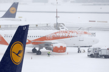 A man shovels snow next to an EasyJet aircraft during a temporary closure at Cointrin airport in Geneva