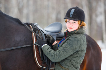 Young woman adjusting stirrups and saddle before riding her bay horse.