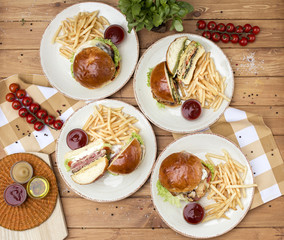 Many different meat burgers, top view. Wooden background