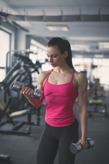 Strong bodybuilder woman doing exercises with dumbbells in gym