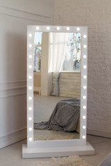 Mirror whith white frame and light bulbs in interior flat. Close up