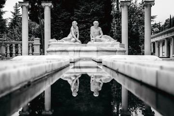 Symmetry black and white composition of four antique columns and two statues sitting near water channel and reflected in water
