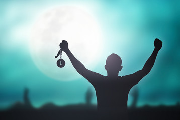 Champion motivator concept: Winner hand raised and holding gold medal reward against full moon on blue night sky background