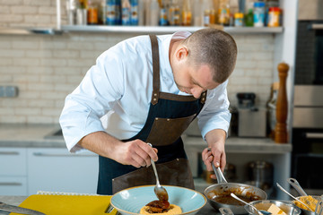 food cooking, profession and people concept - male chef cook serving plate of polenta and veal tongues with sauce at restaurant kitchen. cooking process