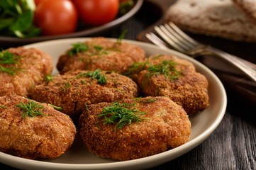Fried meat cutlets, tomatoes and salad on wooden background.