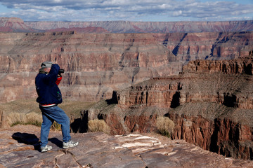 A visitor takes pictures at Eagle Point on the west rim of the Grand Canyon