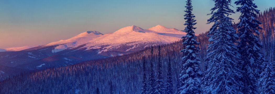 Winter mountain landscape with the top mountains lit by sunset. Panoramic photo.