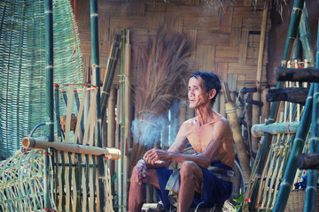 Thailand Father old man smoking after working hand made Basket bamboo or fishing gear. Local life country Thailand