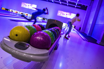A guy and a girl are playing bowling. Neon light in bowling Club. Rack with balls for bowling.  Bowling strike.