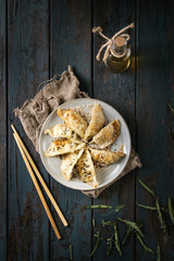 Asian dumplings Gyozas potstickers fried on ceramic plate, served with chopsticks and bottle of sauce over dark wooden plank background. Top view, space. Dark rustic style