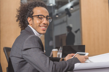handsome young architect in suit sitting at workplace at office and using tablet